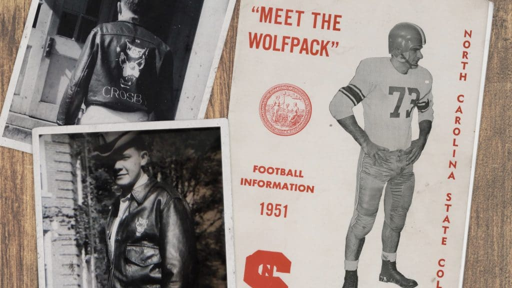 """A flat-lay image shows two black-and-white snapshots of a man wearing a Wolfpack leather jacket, along with a brochure that says """"Meet the Wolfpack. Football Information. 1951."""""""