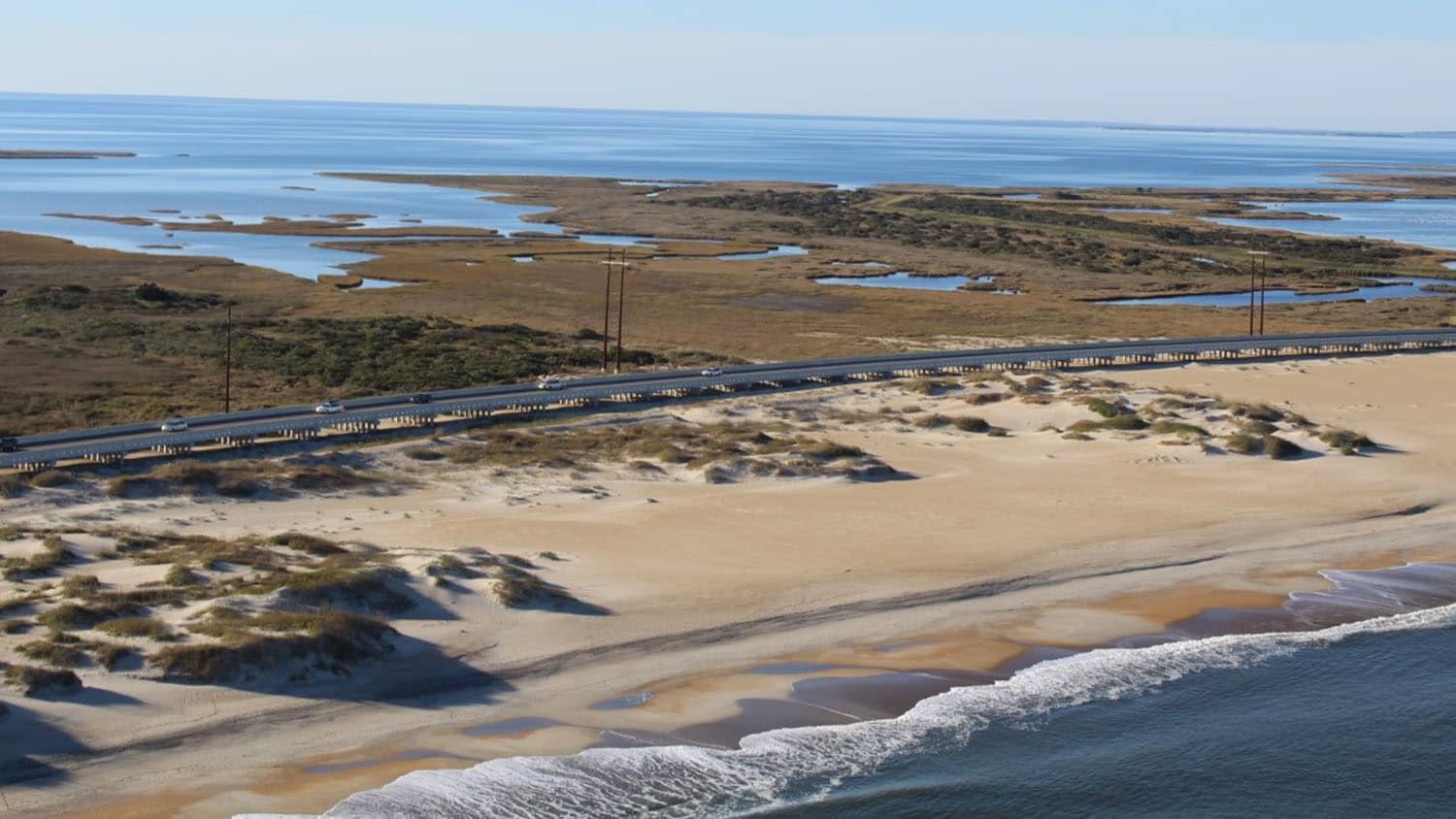 aerial photograph of the ocean, beach, dunes, a highway, and then wetlands