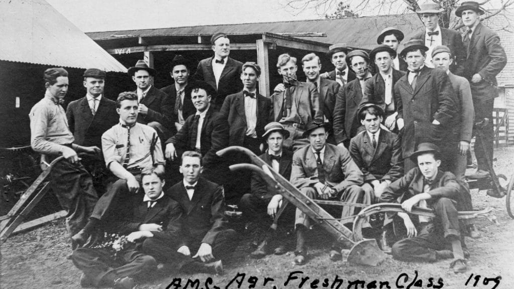 """A black and white photo of a group of men posing with farming equipment. The bottom of the photo reads """"Freshman Class 1909."""""""