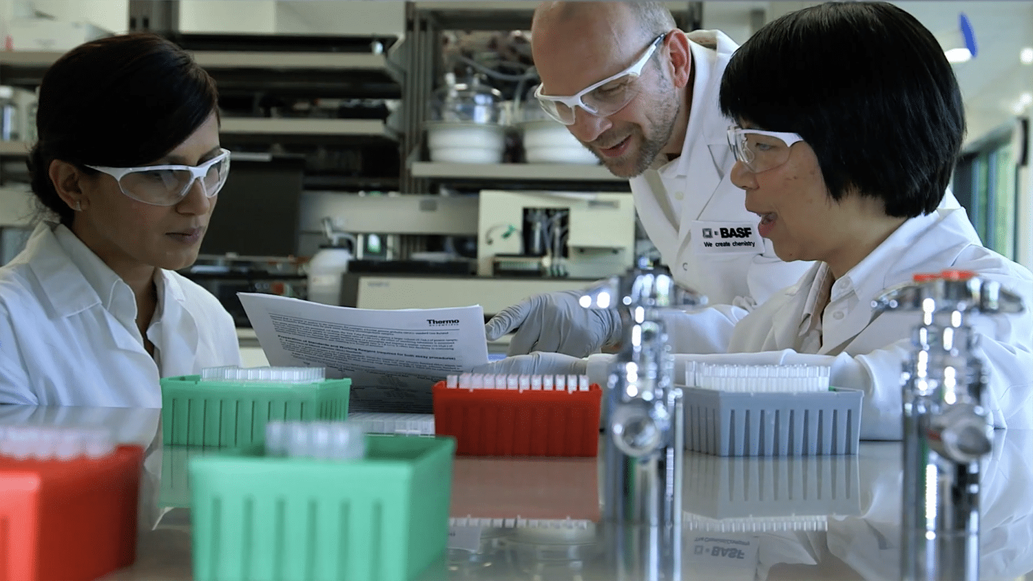 Three BASF researchers work in a lab, all wearing white lab coats.