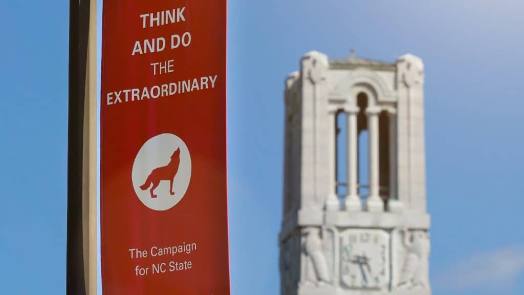 """Hanging near the Memorial Belltower, a red banner with a wolf logo reads """"Think and Do the Extraordinary: The Campaign for NCState."""""""