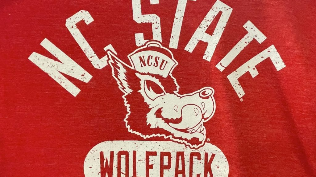 A red shirt features a logo of a wolf with a drooling tongue sticking out.