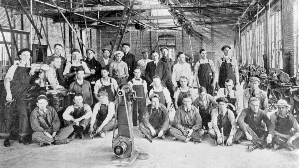 A black and white photo of a group of men wearing overalls, posing in a warehouse.