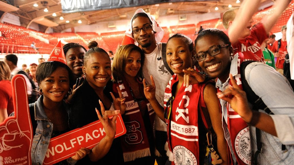Student from the 2010s wear Wolfpack scarves during NCState's 125th birthday party in Reynolds Coliseum.