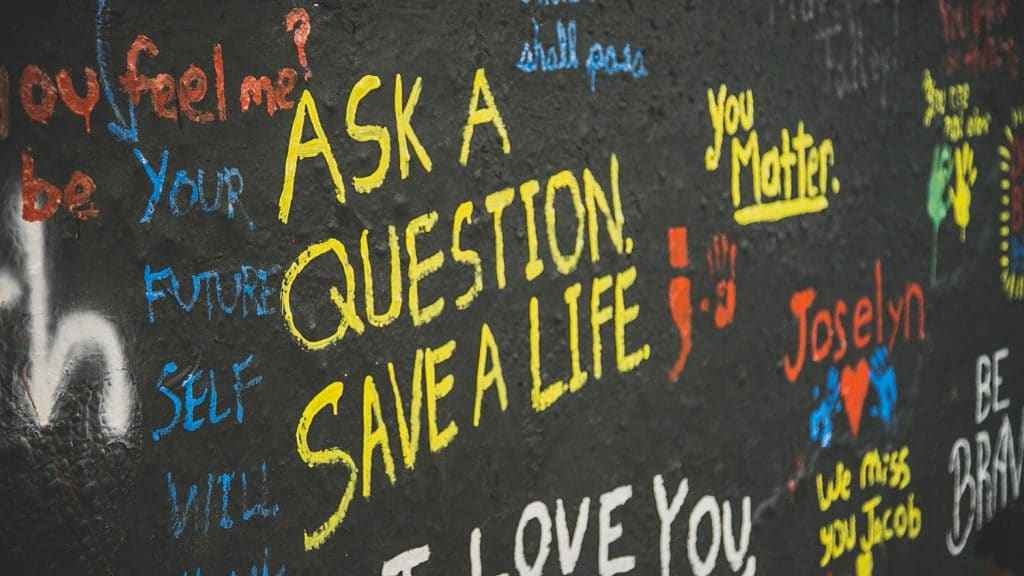 """A wall in the Free Expression Tunnel painted with phrases including """"Ask a Question, Save a Life""""; """"You Matter""""; and """"I Love You."""""""
