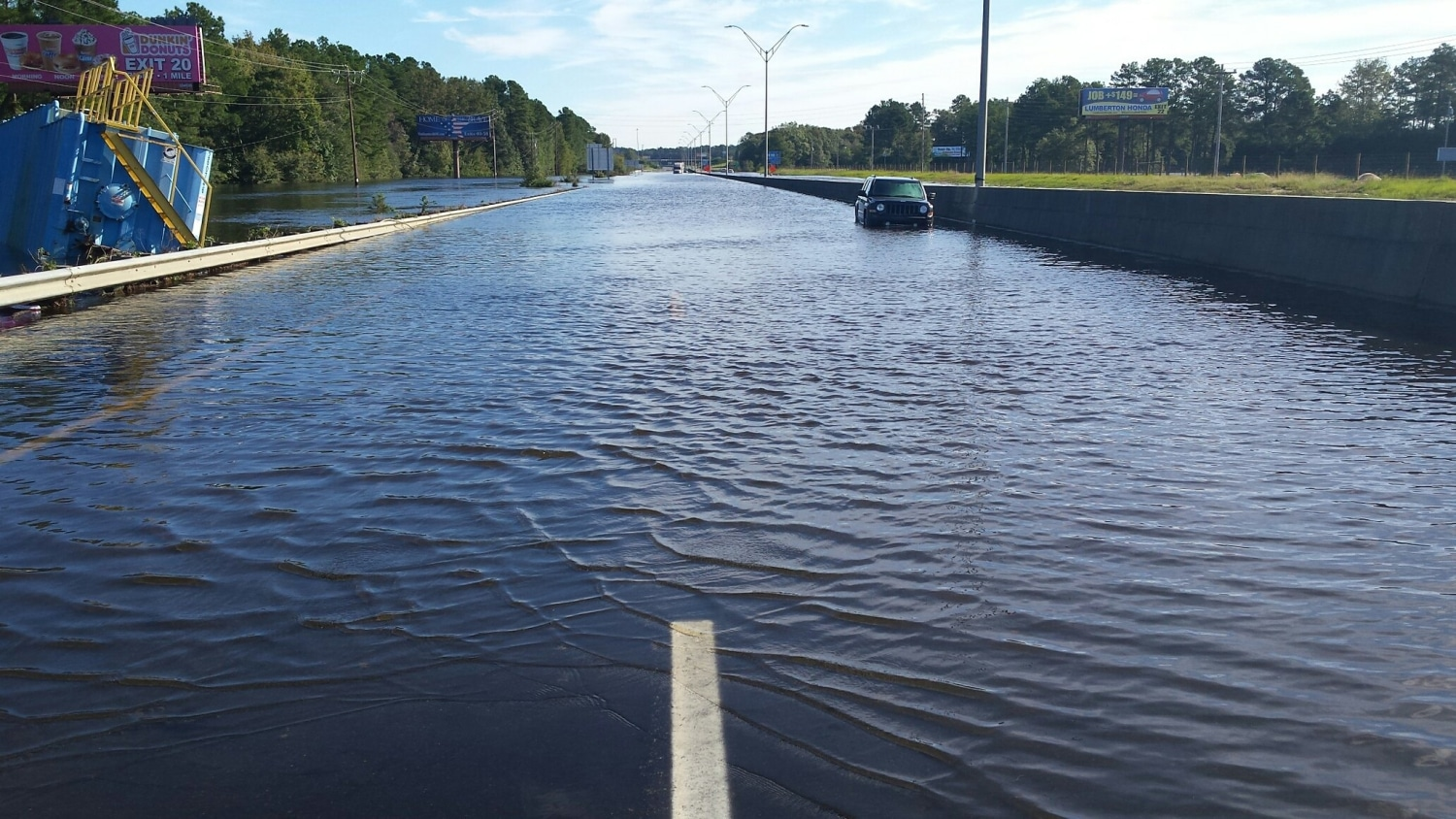 a two-lane road disappears into floodwaters