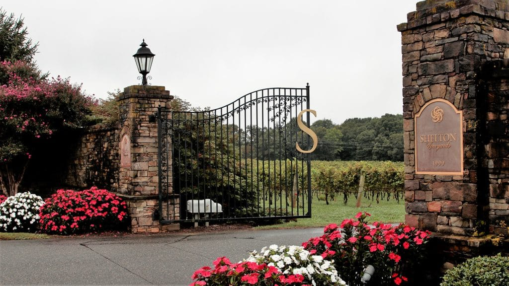 The vineyards front gates with flowers blooming in beds on either side of the entrance.