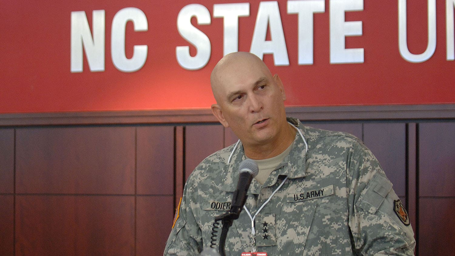 Ray Odierno seated with large sign behind him reading NC State.